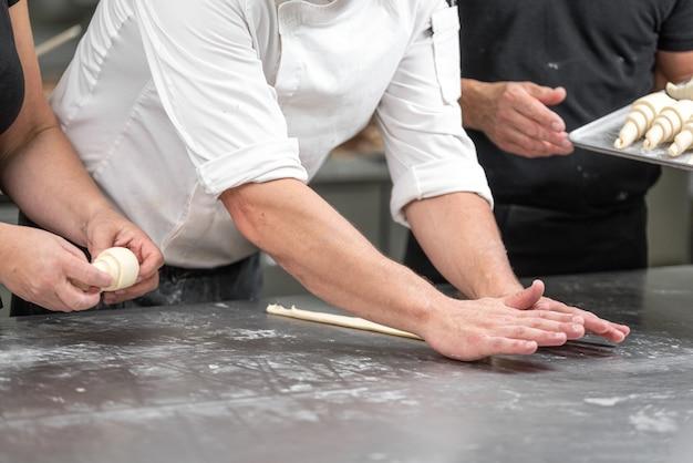 Baker concept. make croissant on table , fresh bakery. Premium Photo
