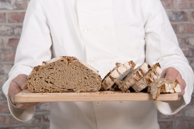 Baker hands with fresh bread on wood table Premium Photo