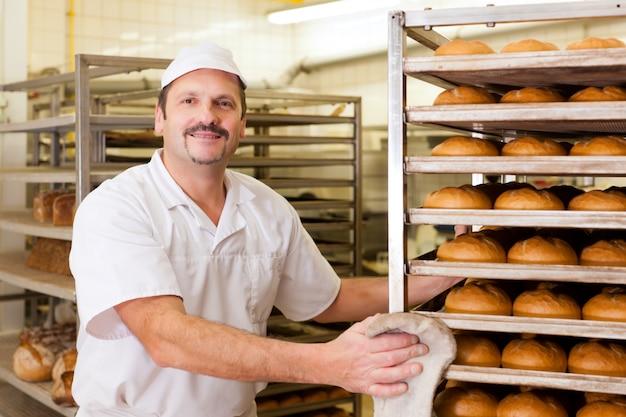 Baker in his bakery baking bread Premium Photo