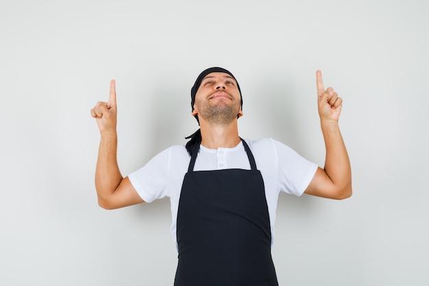 Tシャツ、エプロンで指を上に向けて感謝しているベイカーの男。 無料写真