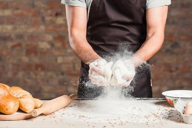 Baker mixing knead dough with flour on kitchen worktop Free Photo