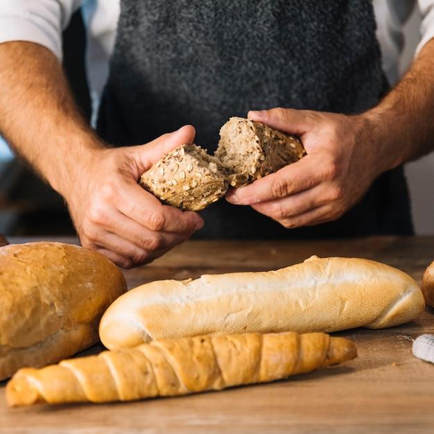 Baker's hand breaking whole grain bread over the wooden desk Free Photo