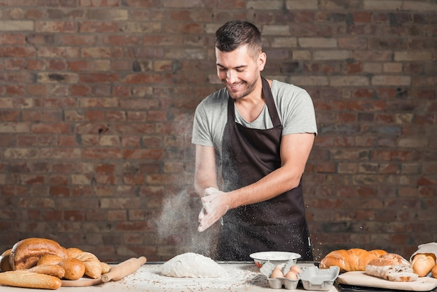 Baker's hand clapping a flour over the kneaded dough on table Free Photo
