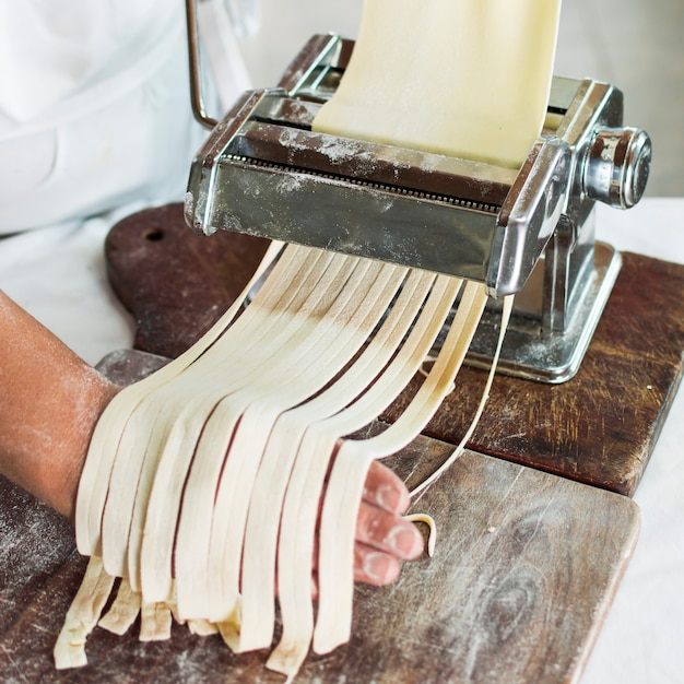 Baker's hand cutting raw dough into tagliatelle on pasta machine Free Photo
