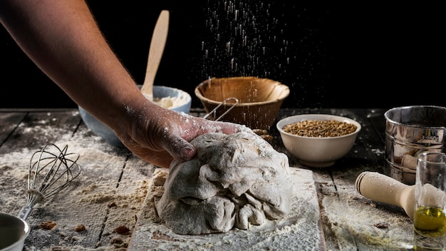 Baker's hand kneading the dough on baking table Free Photo