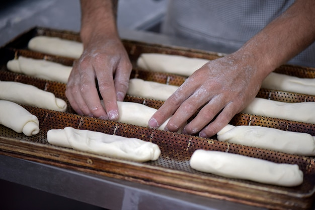 The baker shapes the bread to be baked Premium Photo