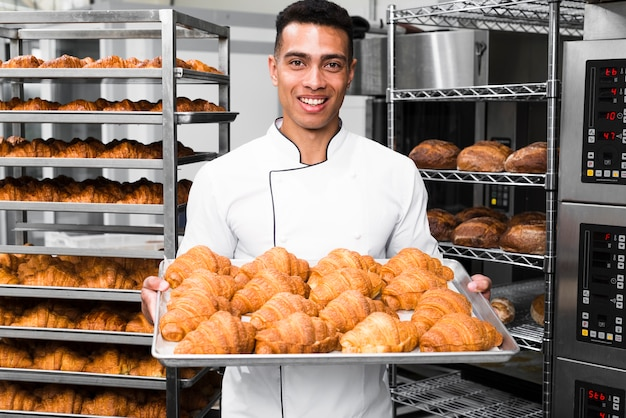 Baker smiling at camera holding tray of croissant in a commercial kitchen Free Photo
