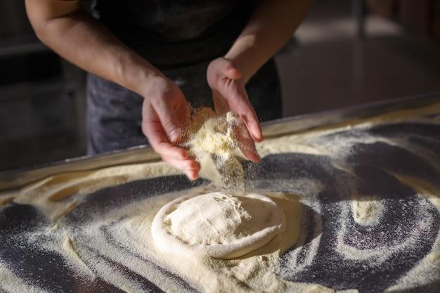 Baker sprinkles dough for pizza by semolina Premium Photo