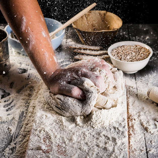 Baker sprinkling the wheat flour on the dough over the kitchen table Free Photo