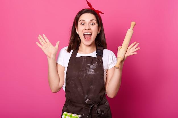 Бейкер молодая женщина поднимает руки, держа скалку, носит коричневый фартук, белую футболку, широко раскрывает рот. очаровательная милая женщина в приподнятом настроении во время приготовления новых блюд. кук концепция. Бесплатные Фотографии