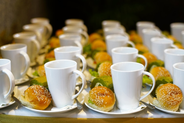 Bakery and beverage on white cup and dish for coffee break time or meal at party Premium Photo