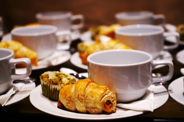 Bakery and beverage on white cup and dish for coffee break time. Premium Photo