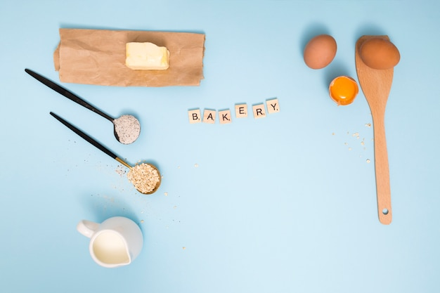 Bakery blocks with butter; milk pitcher; oats barn; flour; eggs and wooden spatula on blue background Free Photo