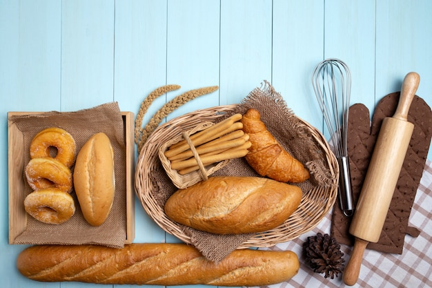 Bakery bread on blue wooden table. various bread and sheaf of wheat ears. Premium Photo