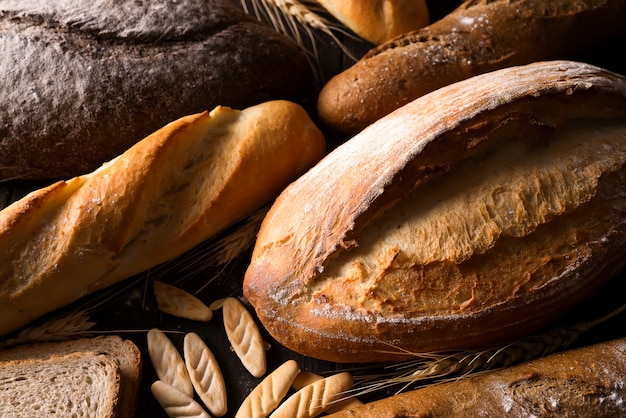 Bakery - gold rustic crusty loaves of bread and buns on black chalkboard background. Premium Photo
