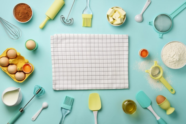 Bakery ingredients over blue background - butter, sugar, flour, eggs, oil, spoon, rolling pin, brush, whisk, towel. Premium Photo