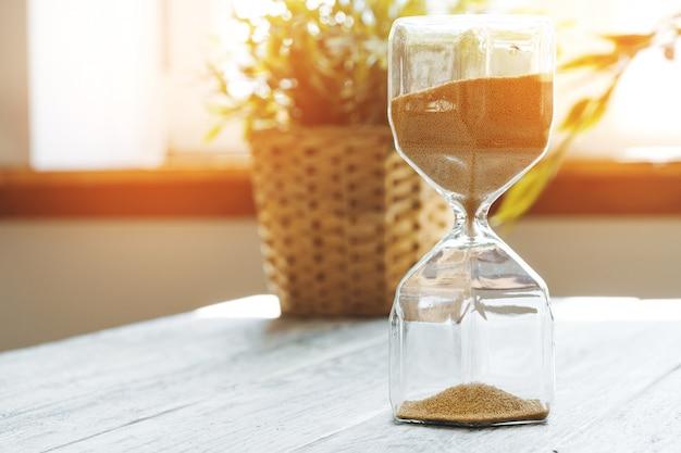 木製bakgroundのクローズアップの砂時計。時間の概念 Premium写真