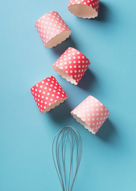 Baking background with pink cake forms on blue background Premium Photo