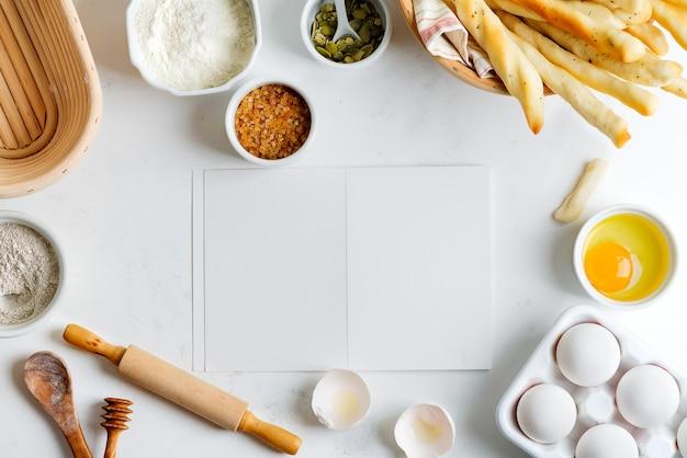 Выпечки ингредиенты для приготовления домашнего традиционного хлеба с бумагой для рецепта на светло-серый мраморный стол. Premium Фотографии