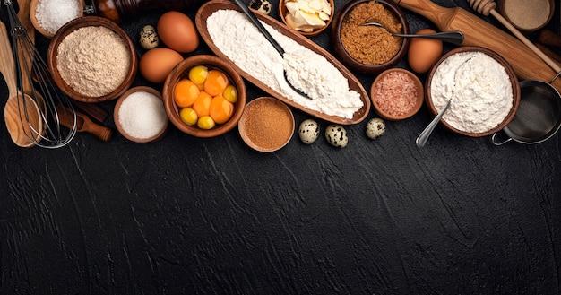 小麦粉、卵、バター、テキストのコピースペースで自家製のベーキングのための砂糖の平面図、黒の生地のベーキング成分 Premium写真