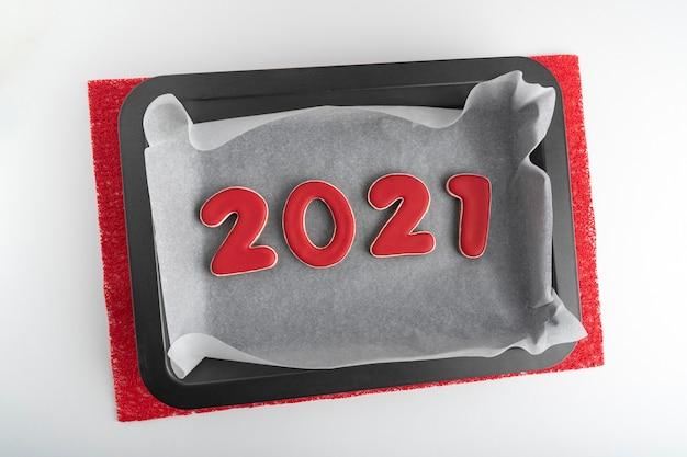 赤いジンジャーブレッドクッキー2021のベーキングシート。大晦日の伝統。 Premium写真