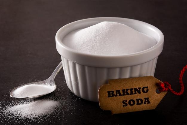 Baking soda in white bowl on black background Premium Photo