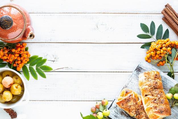 白い木製のテーブルの上で、リンゴ、焼きたてのリンゴ、パイ生地から作られたシナモンロールで焼く。上面図、素朴なスタイル、コピースペース。 無料写真