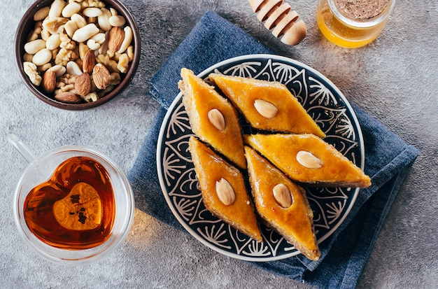 Baklava. ramadan dessert.arabic dessert with nuts and honey, cup of tea on a concrete background. Premium Photo