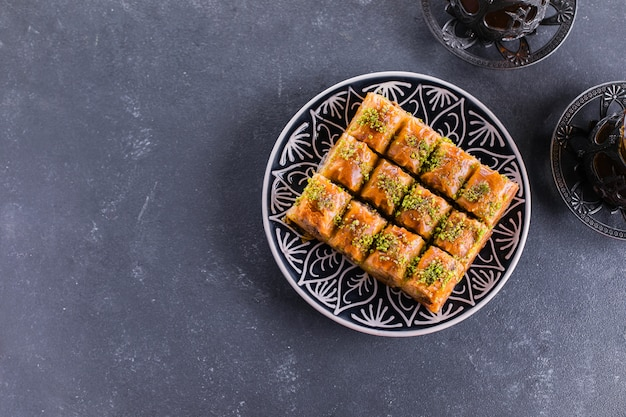 Baklava. ramadan dessert. traditional arabic dessert with nuts and honey, cup of tea on a concrete table. top view, copy space Premium Photo