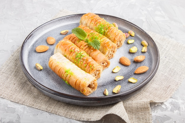 Baklava, traditional arabic sweets in gray ceramic plate close up. Premium Photo