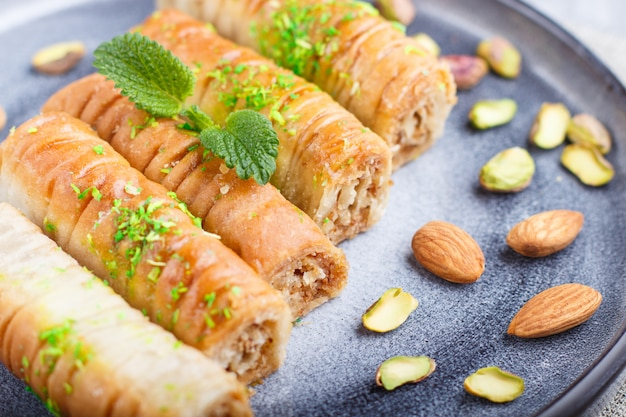 Baklava, traditional arabic sweets in gray ceramic plate on a gray concrete background. Premium Photo