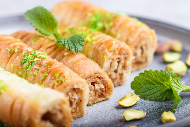 Baklava, traditional arabic sweets in gray ceramic plate on a gray concrete. close up. Premium Photo