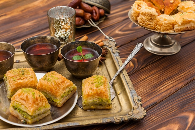 Baklava with tea cups on tray Free Photo
