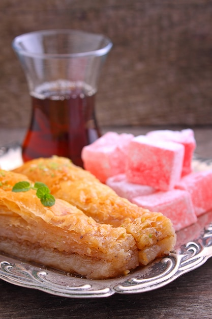 Baklava with walnuts and turkish delight with tea in turkish Premium Photo