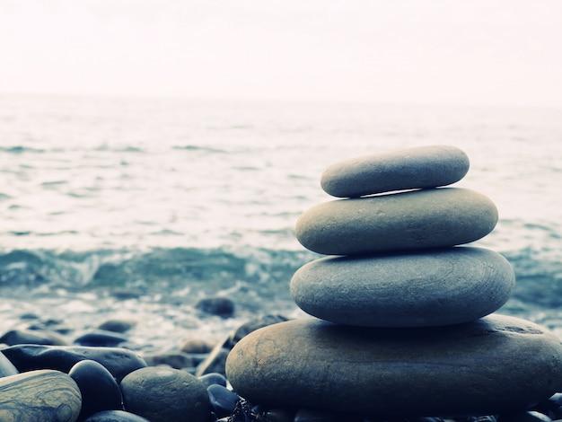 バランス、心の安らぎ、さまざまなサイズの石がピラミッドを形成し、小石のビーチにある石のピラミッドは、安定性、禅、調和、バランスを象徴しています。浅い被写界深度。 Premium写真