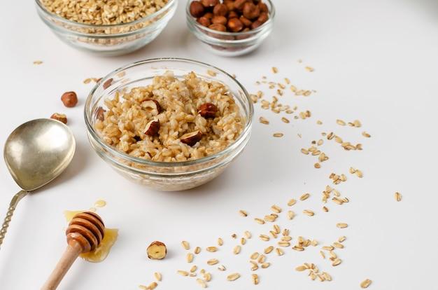 Сбалансированное диетическое меню на завтрак с овсяной кашей, миской с фундуком и медом Premium Фотографии