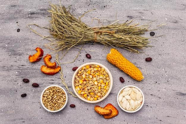 国内の齧歯類のためのバランスの取れた食事。穀物と種子、ドライハーブ、新鮮な果物の盛り合わせ Premium写真