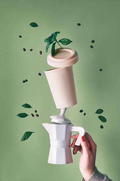 Балансировка ноль отходов кофе пирамиды, проведенные женской рукой на фоне зеленой мяты. керамическая кофеварка для приготовления эспрессо и экологически чистая многоразовая бамбуковая кофейная кружка. кофе в зернах и листьев растений. Premium Фотографии
