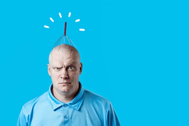 Bald brutal man scratching his head with a special device on blue Premium Photo