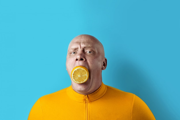 Bald brutal man with lemon in his mouth and yellow jacket on blue background Premium Photo