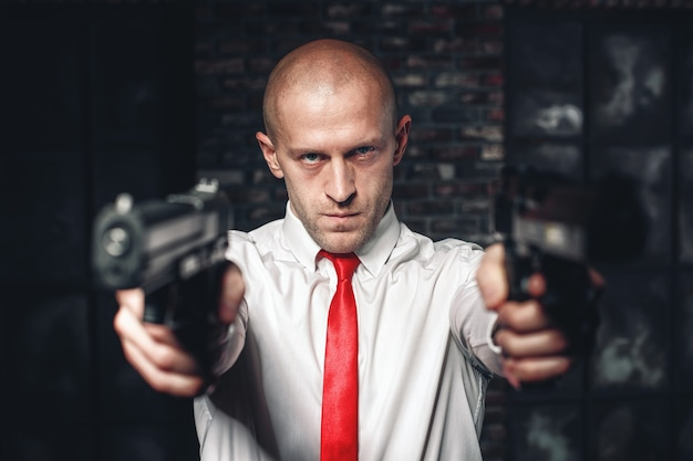 赤いネクタイでハゲを雇ったキラーはピストルを狙う Premium写真