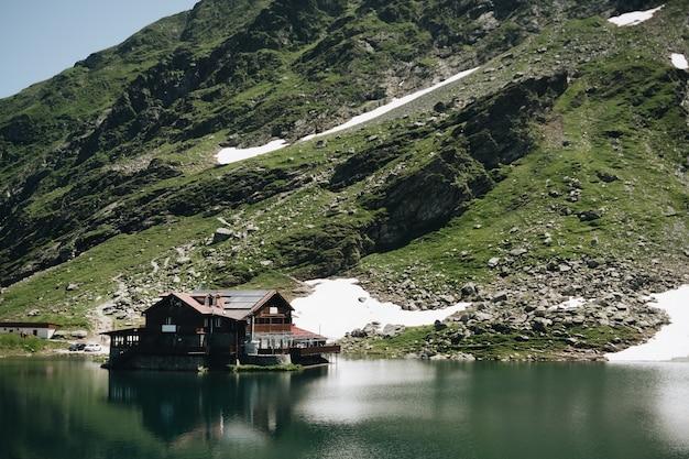 Взгляд ландшафта озера balea в горах румынии и fagaras в лете с снежными пиками Бесплатные Фотографии