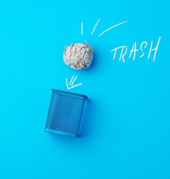 Шар из мятой серой бумаги и металлической синей мусорной корзины Premium Фотографии