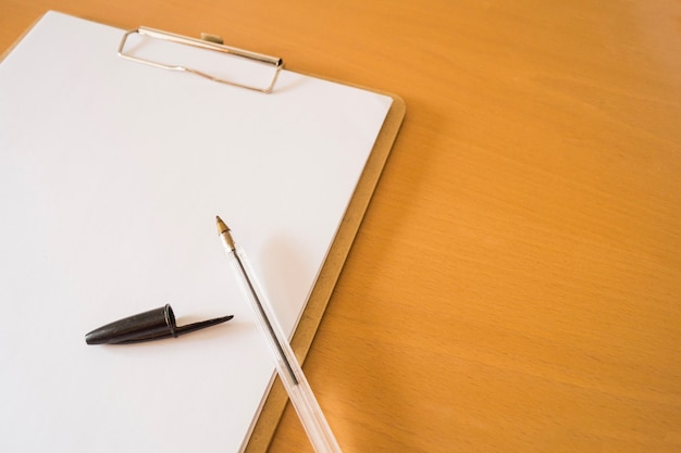 Ball pen and clipboard with papers Free Photo