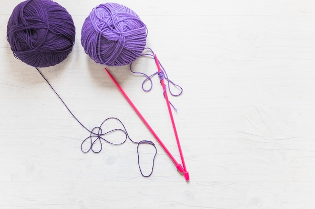 Ball of yarn with pink knitted needle on white textured backdrop Free Photo
