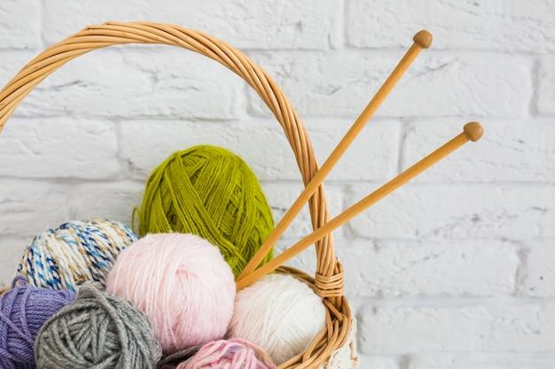 Ball of yarns with crochet in wicker basket Free Photo
