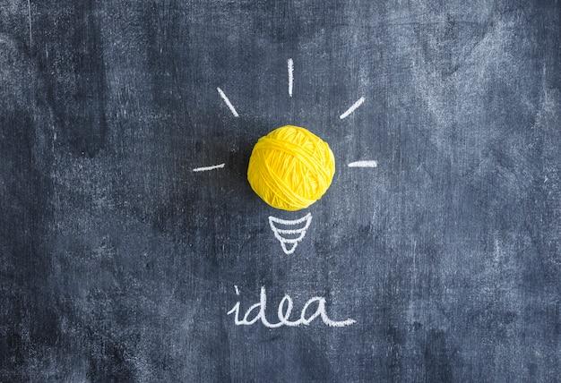 Ball of yellow yarn with idea text on chalkboard Free Photo