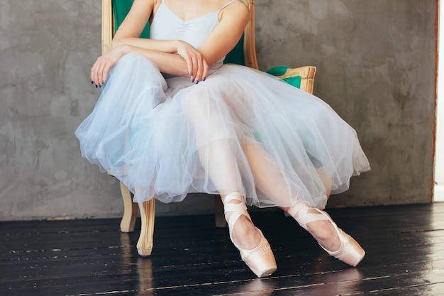 The ballerina ballet dancer in tutu skirt and pointe shous sitting on the classic chair Premium Photo