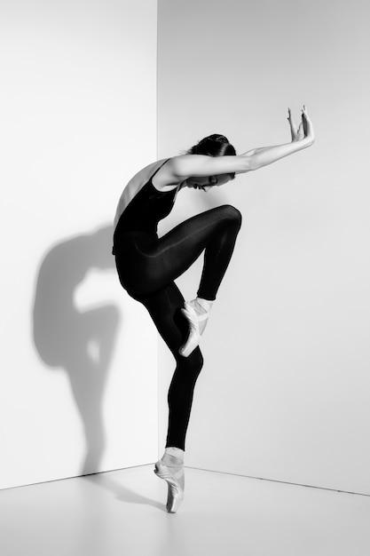 Ballerina in abito nero in posa su scarpe da punta Foto Gratuite