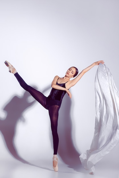 Ballerina in black outfit posing on toes, studio background. Free Photo
